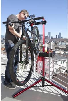 Biker arbeitet mit einem Fahrrad Montageständer